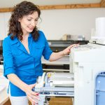 Adult woman checking printer in office